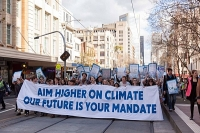 "young people rallying behind an aycc banner declaring ""aim higher on climate, our future is your mandate"""