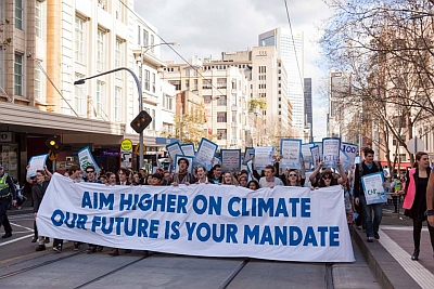 """young people rallying behind an aycc banner declaring """"aim higher on climate, our future is your mandate"""""""