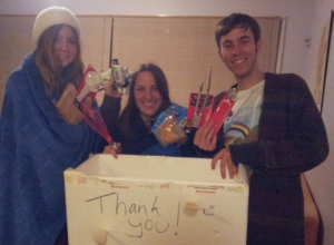 three people holding generous gifts with a sign saying thank you