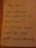 """A note that reads """"hey twit, ever notice how this space fits 2 small cars?? or just one stupid small car that parks inconsiderately"""""""